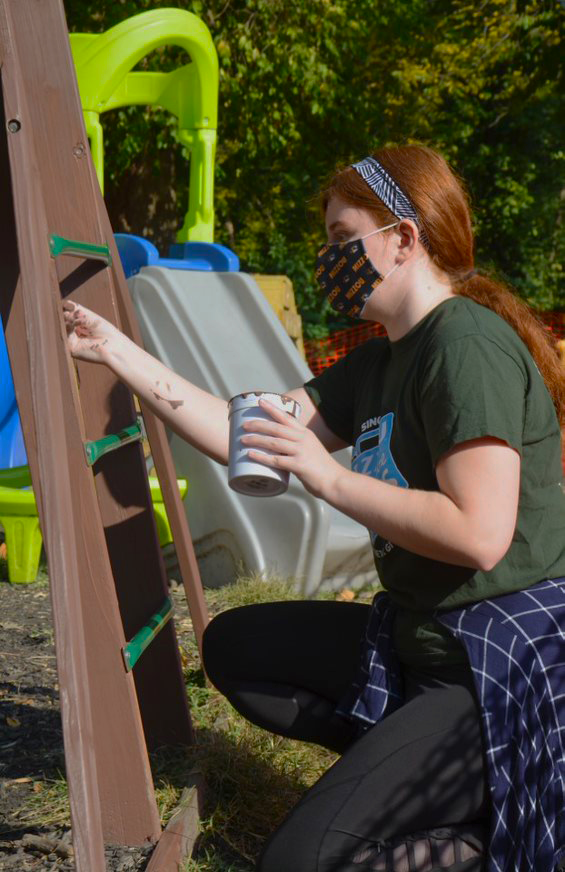This is an image of Mizzou Alternative Breaks participant Emma Wickland painting.
