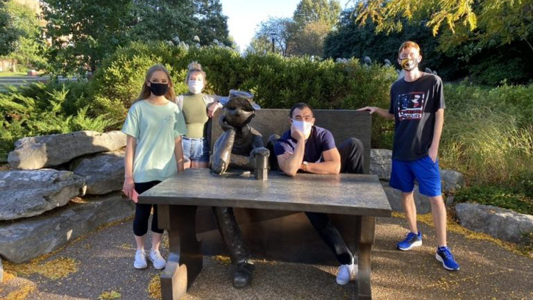 four students wearing face coverings posing around beetle bailey statue