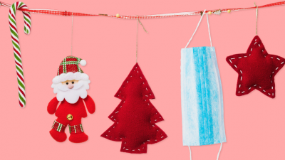 pink background with a garland that has a candy cane, santa, tree, face covering and star hanging off of it