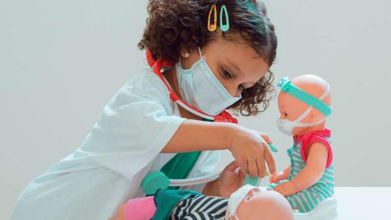a young girl dressed as a doctor, caring for her dolls