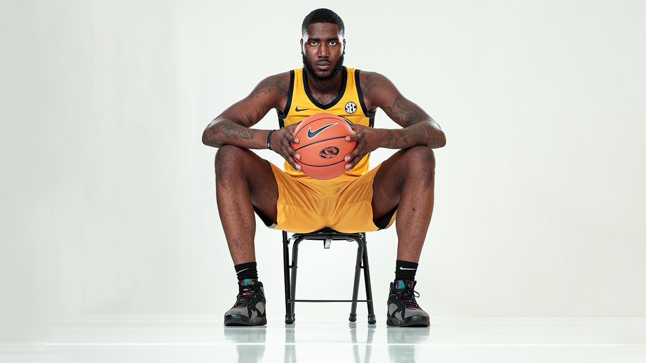 tilmon sitting on a bench, holding a basketball