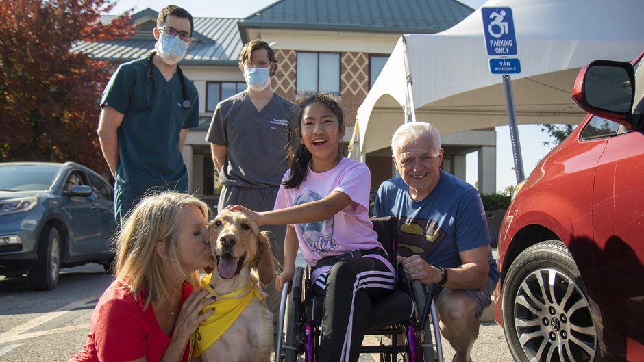 girl in wheelchair with her mom, dad and service dog, with two veterinary health employees in the background
