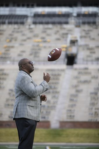 chatman on a football field tossing a ball up, in a grey suit and dark pants
