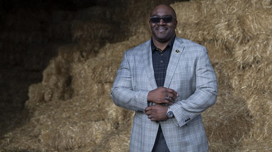 darryl chatman in front of bales of hay