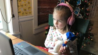 a little girl at a computer with headphones on