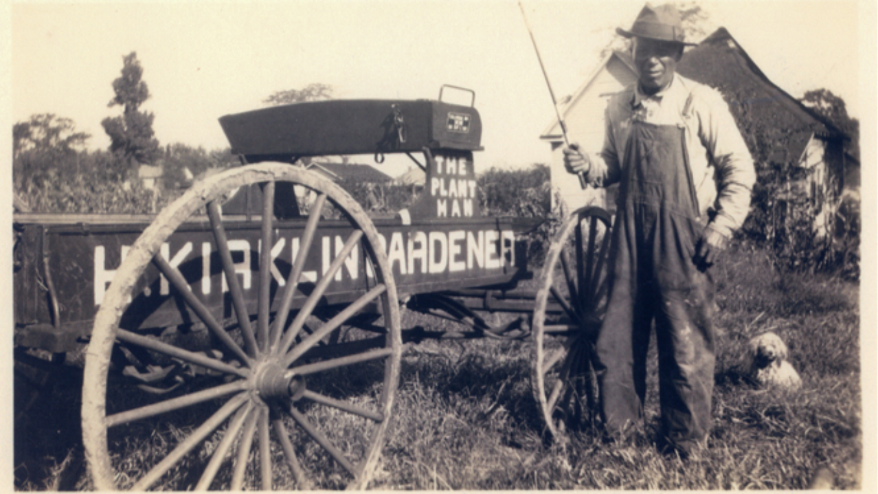 This is a picture of Henry Kirklin standing nwext to his cart.