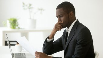 Black man sitting at a desk with a laptop, looking at a piece of paper