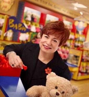 woman in a build-a-bear shop with a bear, holding a felt heart