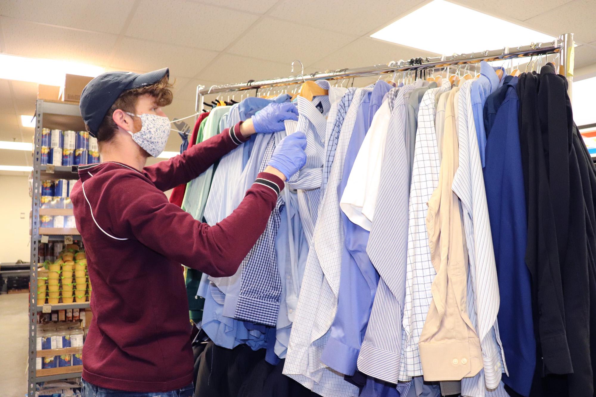 man pulling a dress shirt from a rack