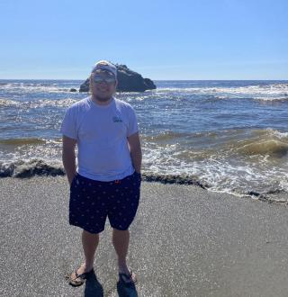 man at the beach smiling for a photo