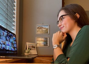 girl sits at a computer on zoom
