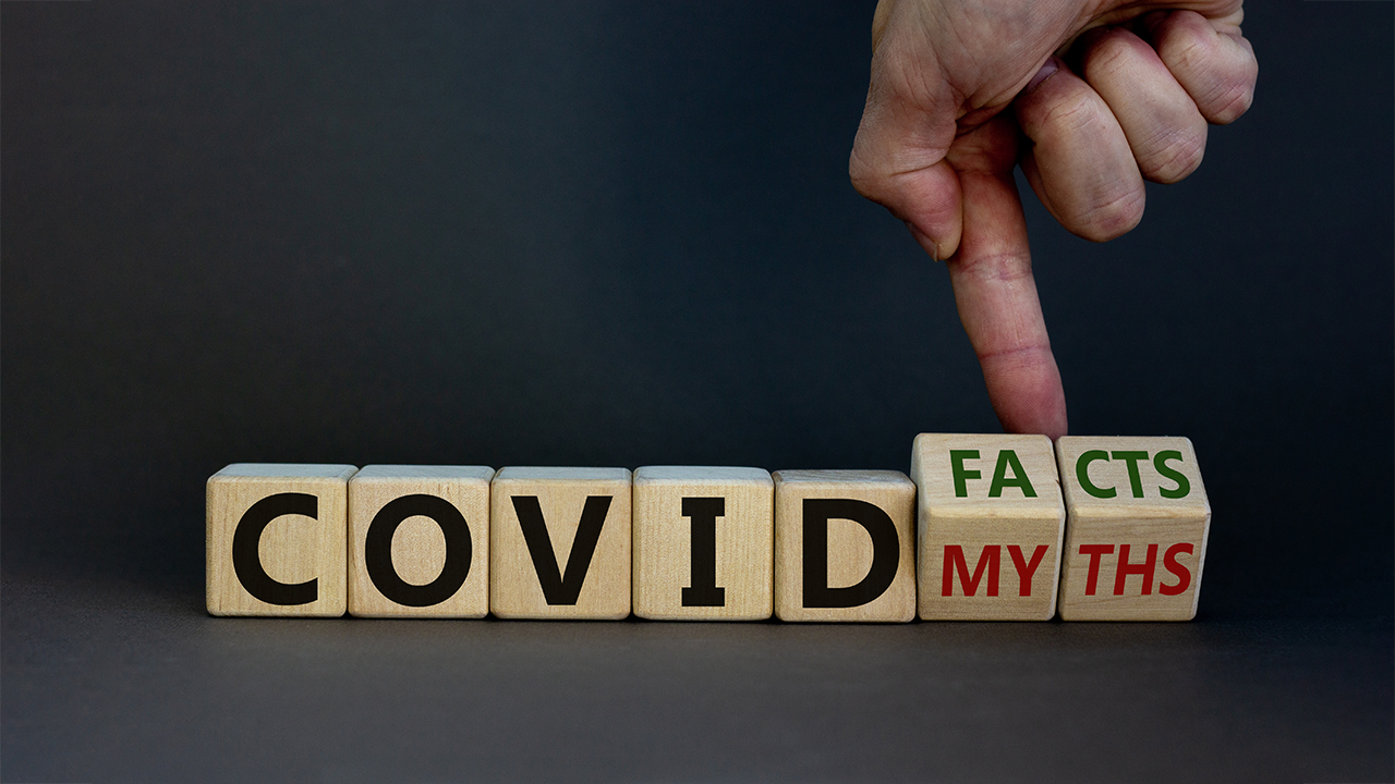 """person pointing to cube letters that spell out """"COVID facts/myths"""" Source: Shutterstock"""