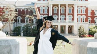 woman in cap and gown in front of the columns