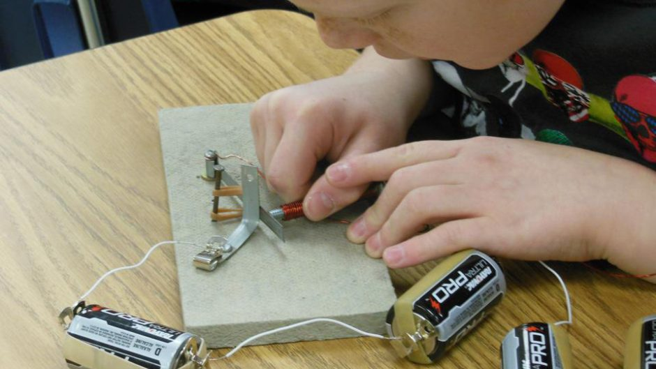 photo of a student working with batteries and tools