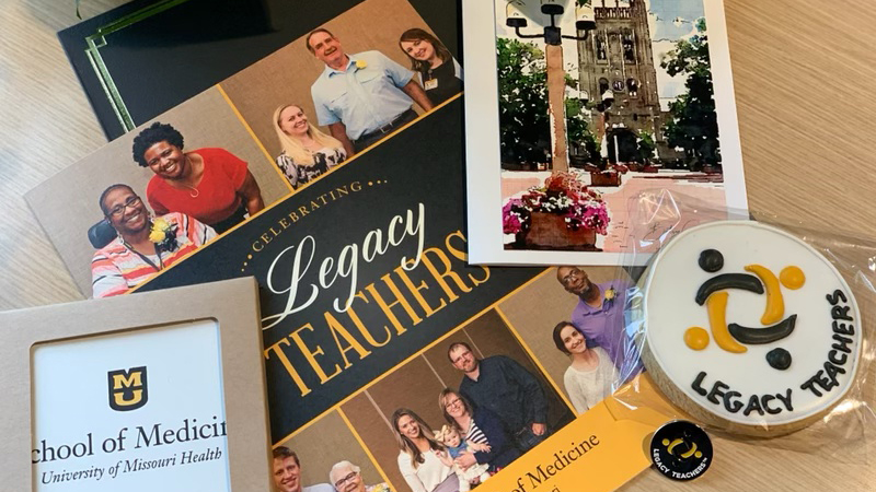 photo of legacy teachers items (photos, cookies, booklet, etc.) on a table