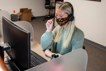 woman with a face covering on the phone at her computer