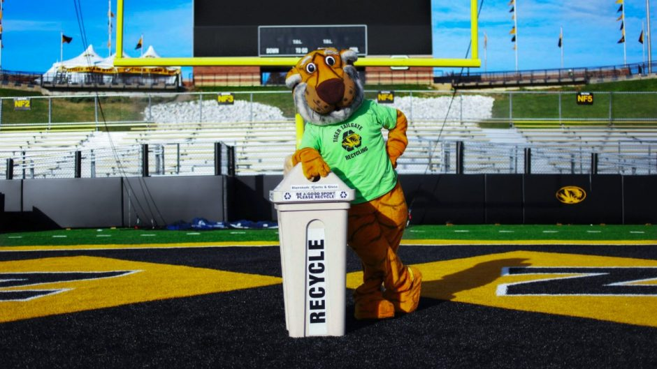This is a picture of Truman the Tiger leaning on a recycling bin.