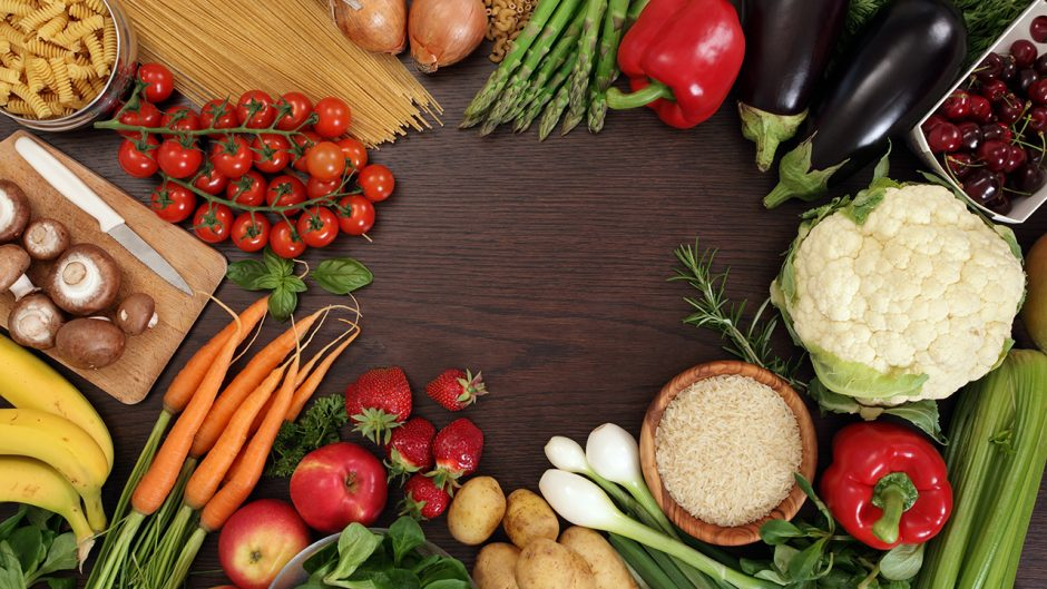 Photo of a table top full of fresh vegetables, fruit, and other healthy foods with a space in the middle for text. Source: Shutterstock