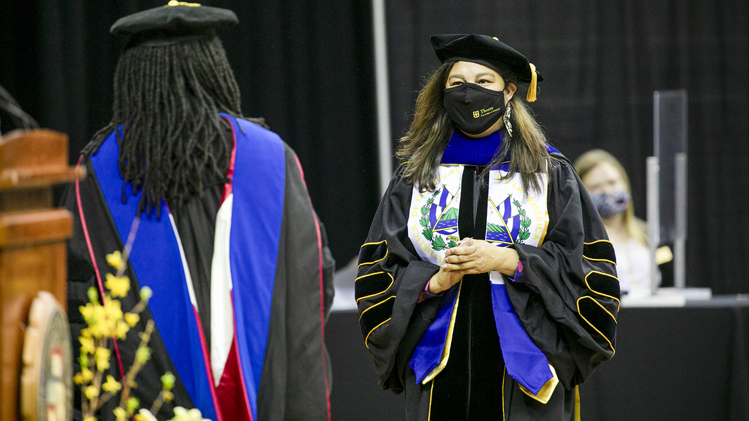 two people in regalia at the ceremony