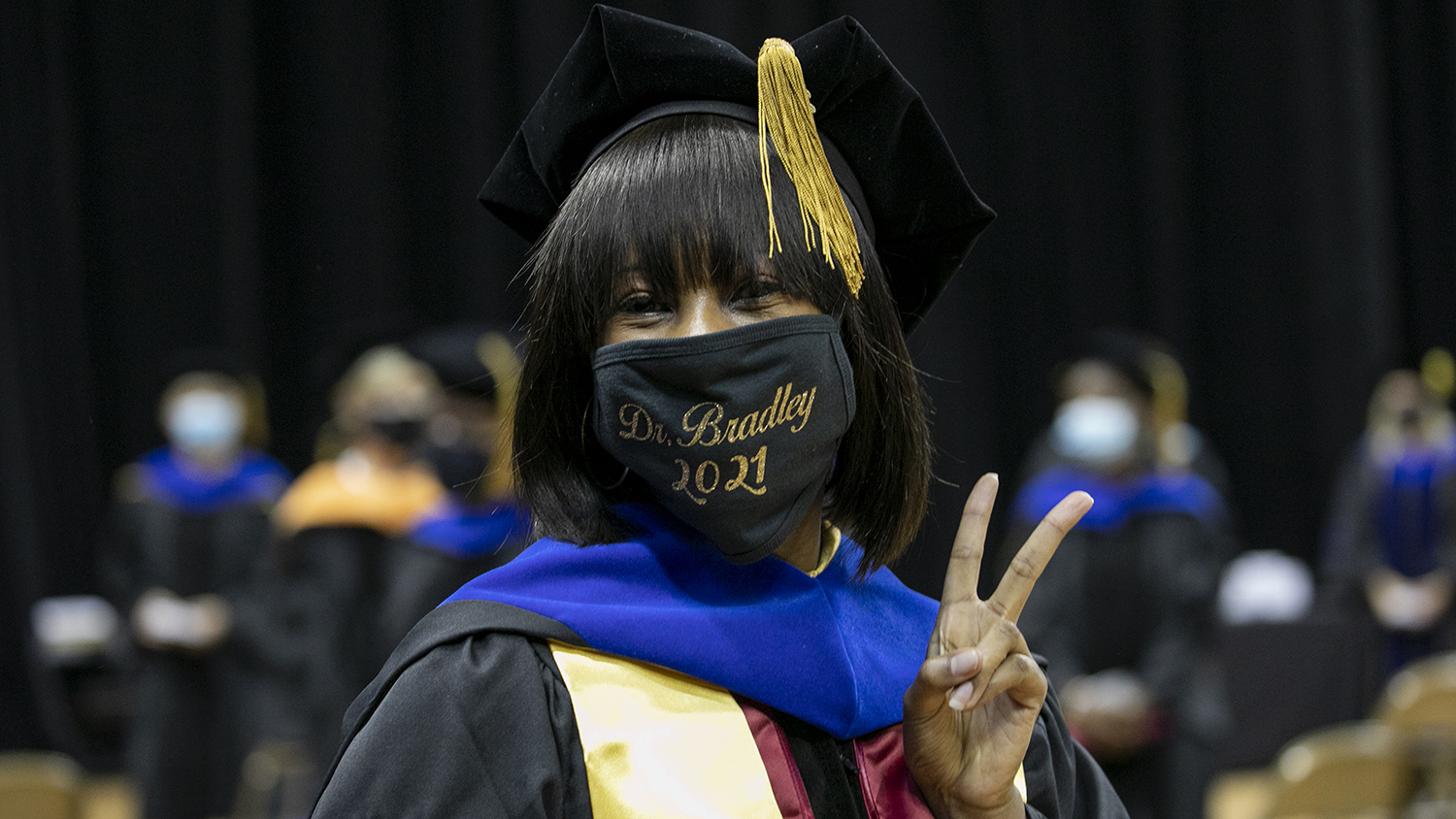 a woman giving the peace sign in her regalia at the ceremony