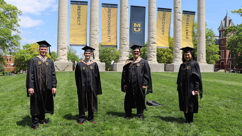 four students in reglia on the quad