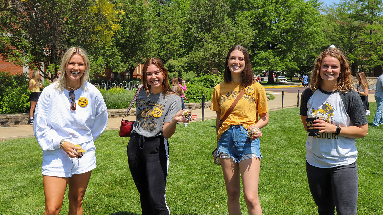 four female students pose on the quad