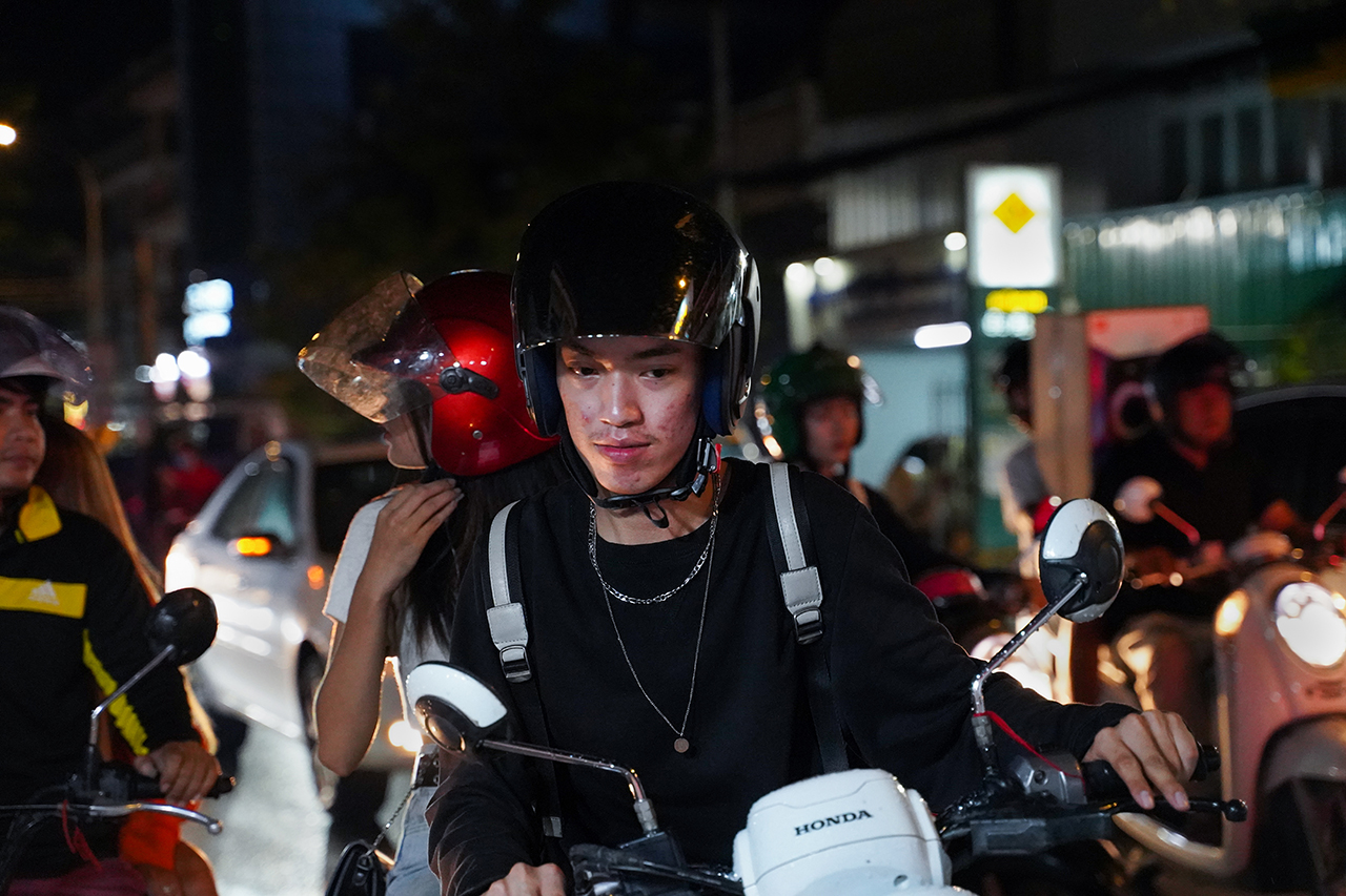 Zing drives his motorbike to get around in Phnom Penh. With only an hour between dancing at the park and starting his night shift at the coffee shop, he hurries along empty roads at night to keep up with his busy schedule. Photo by Cindy Liu