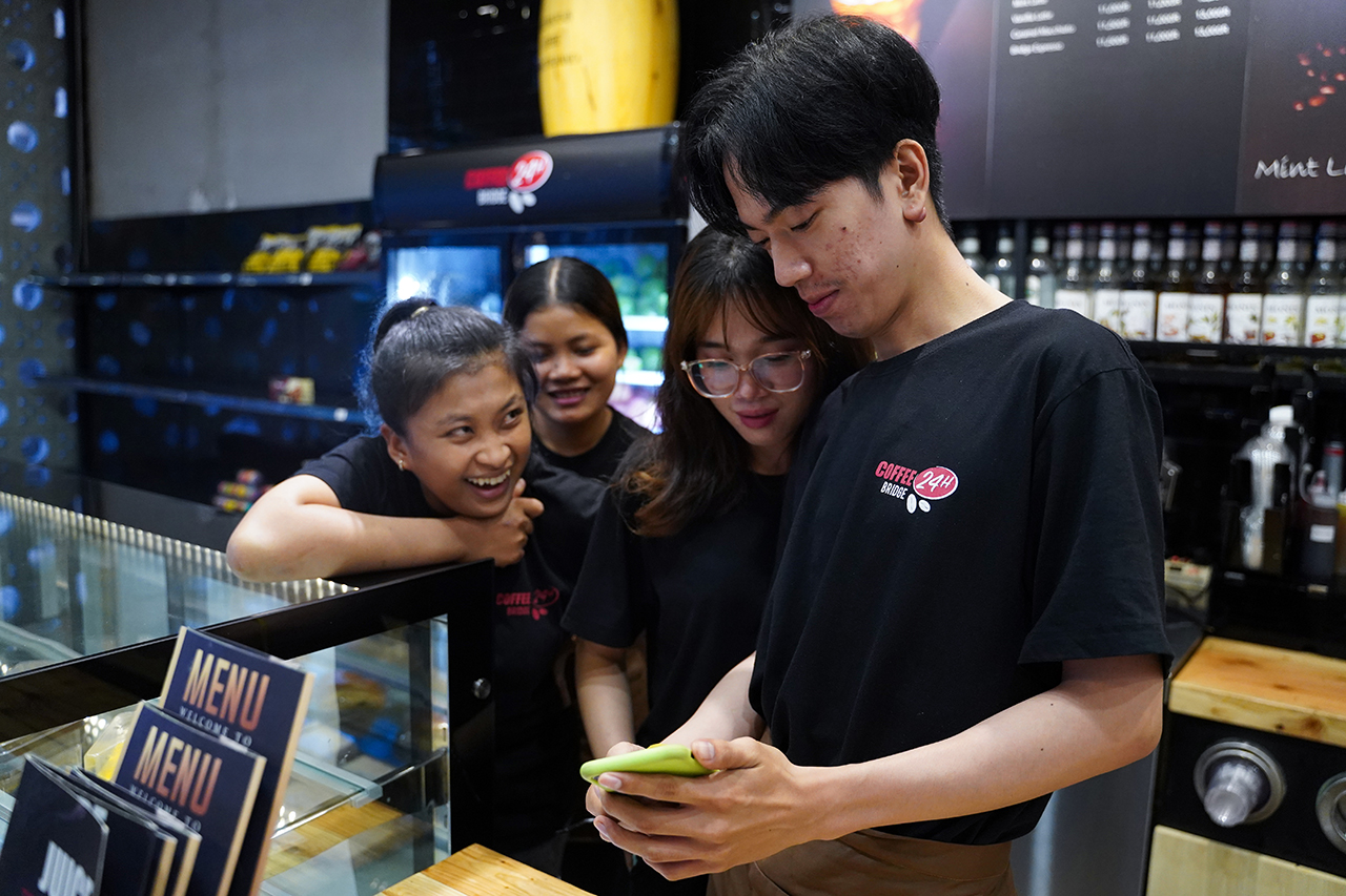 Zing shares a video of one of his dance performances with co-workers at the coffee shop. A co-worker described him as someone who is hard-working and likes to help others. Photo by Cindy Liu