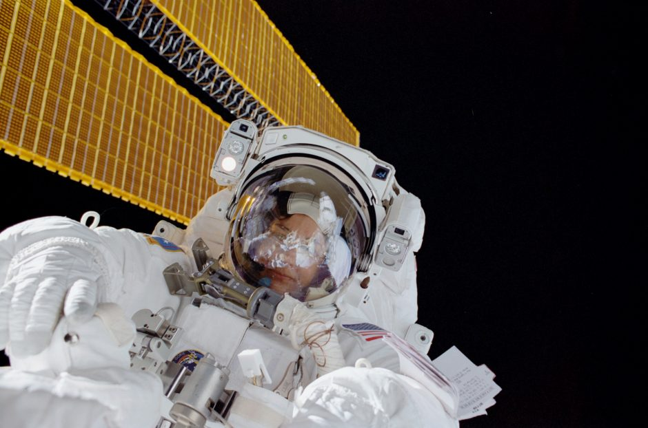 Linda Godwin during extra vehicular activity (spacewalk) during the STS108 space shuttle mission. The shuttle is docked to the International Space Station; the ISS solar panels are seen in the background.
