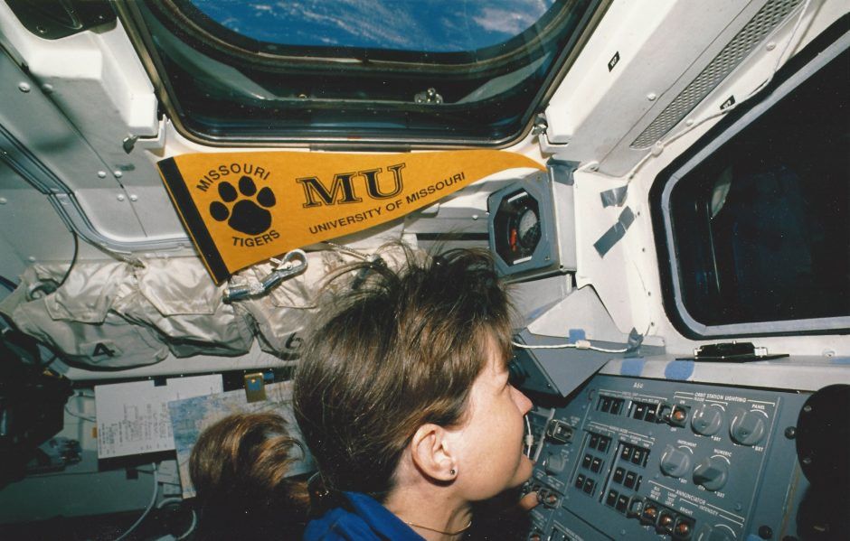 Godwin carried an MU banner to space, seen here displayed on the space shuttle aft flight deck. Earth is visible in the background though the overhead window.