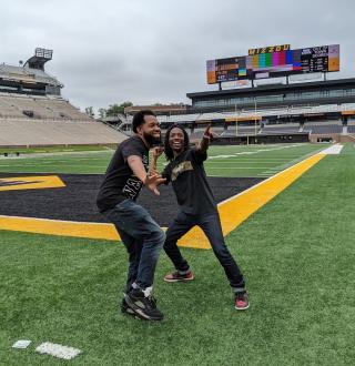 two men posing on a football field