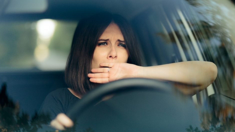 Woman yawning behind the wheel of a car. Source: Shutterstock