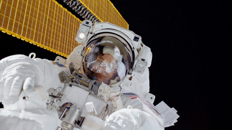 Linda Godwin during extra vehicular activity (spacewalk) during the STS-108 space shuttle mission. The shuttle is docked to the International Space Station; the ISS solar panels are seen in the background.