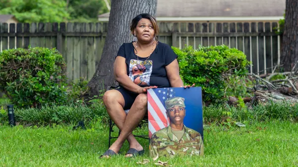 a woman poses for a portrait with a photo of her son