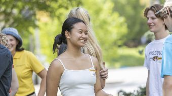 a girl in a white tank top smiles in the center of the photo. there are other students around her