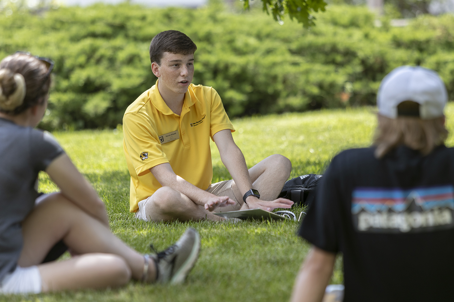 a young man in a yellow shirt sits in a circle with other students whose backs we see