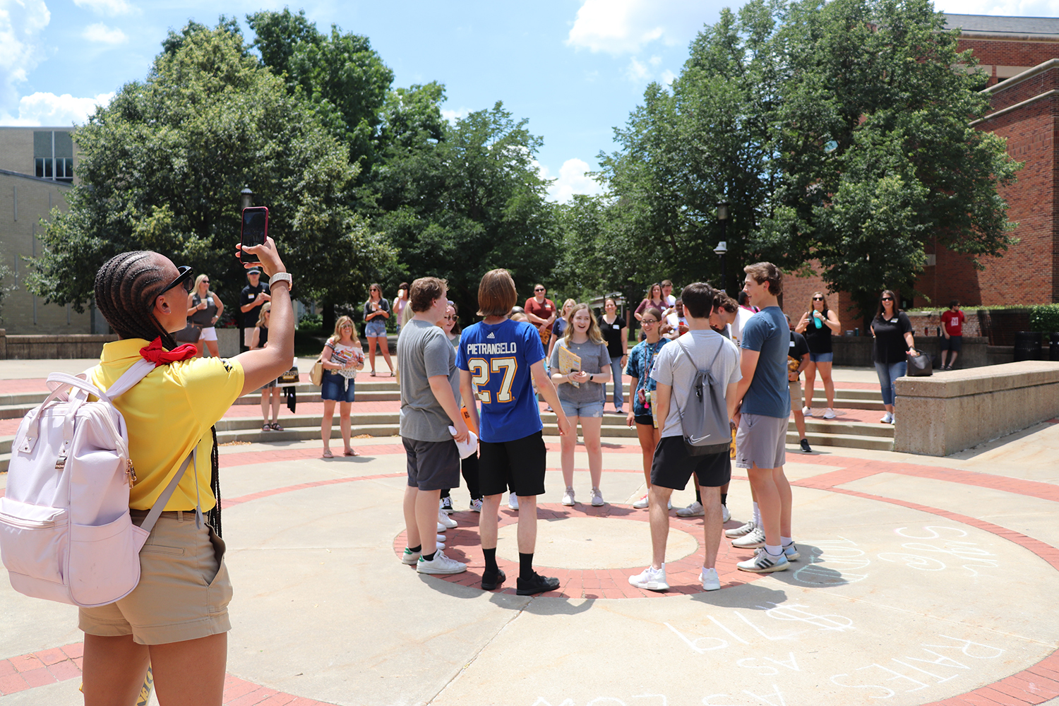 a young woman takes a photo of a group of students who are standing and smiling in speaker's circle