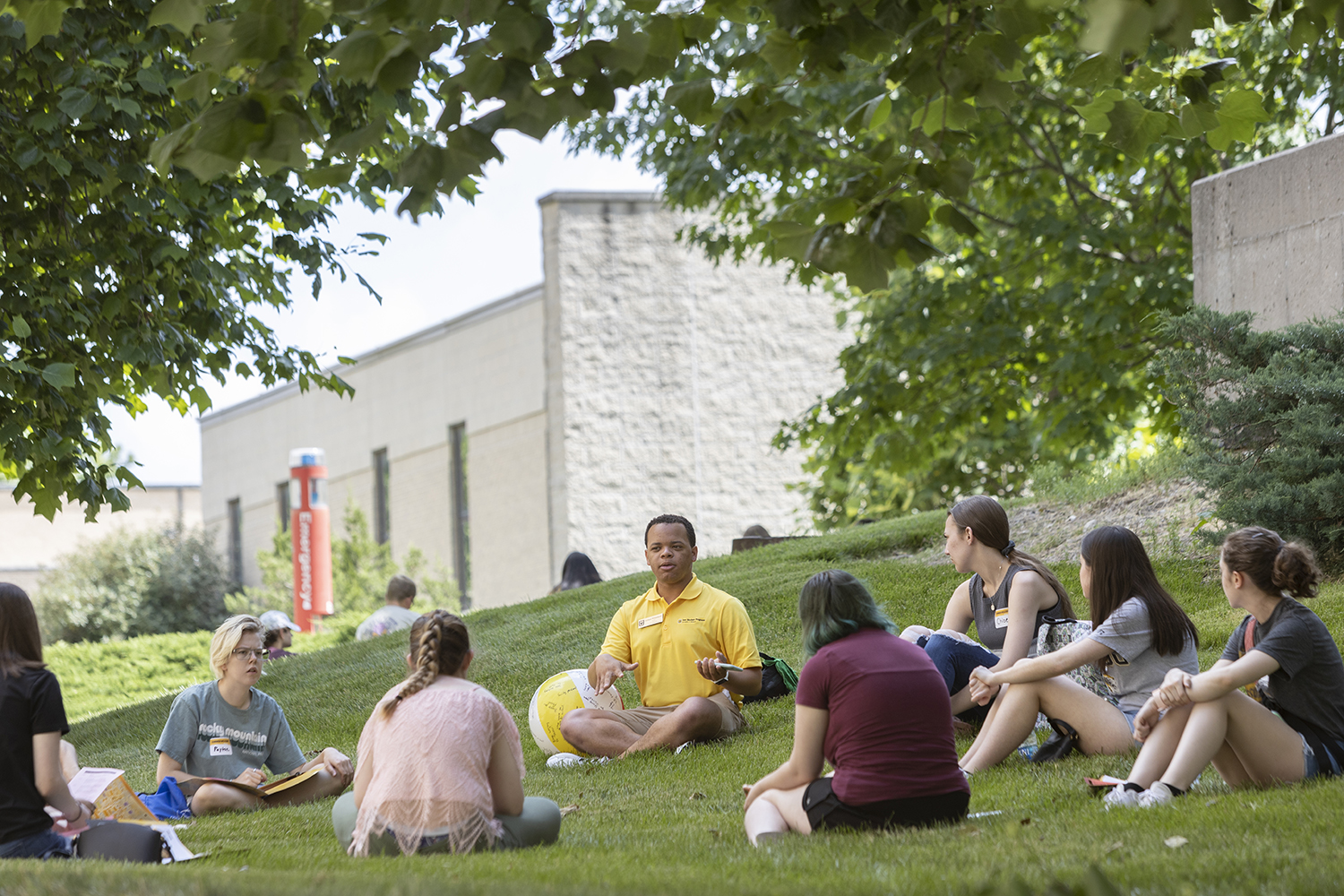 a male student sits at the center of a circle of students. they're sitting outside under trees on a sunny day