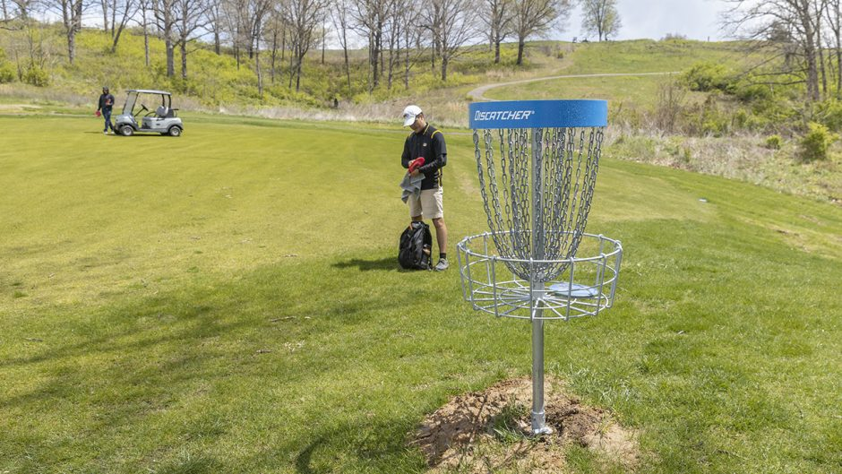 Michael Natera, member of the Mizzou Disc Golf Club, cleans off his disc at the new course.