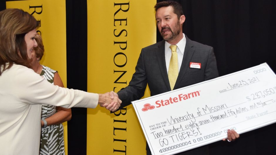 This is a photo of Jackie Lewis shaking hands with a State Farm representative.