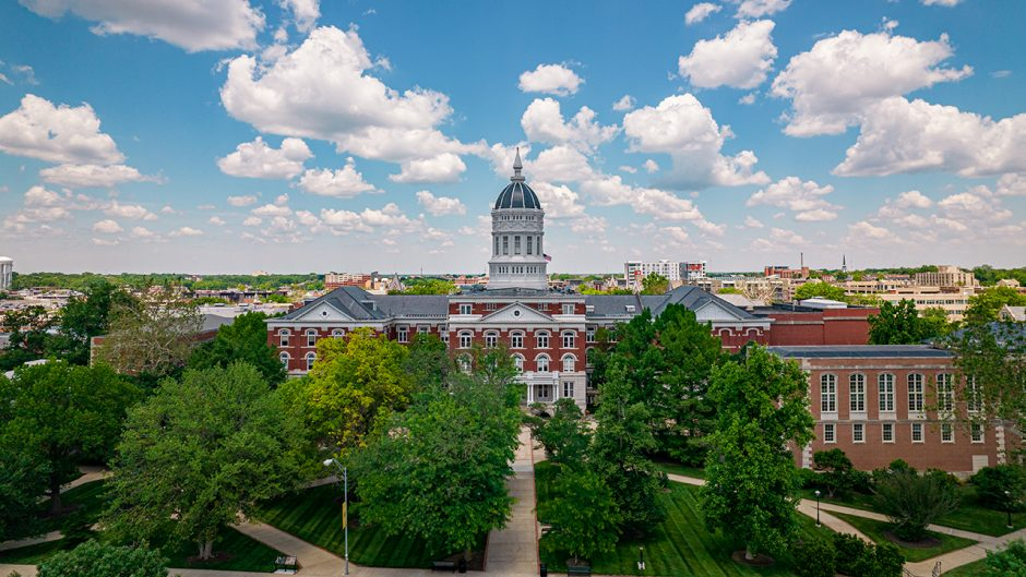 drone shot of jesse hall with lush, green trees in front of it during summer