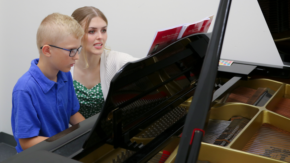 This is an image of a teacher teaching her student about the piano.