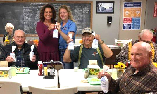 Aly Francis, standing at right, presents ground pork from her barrows to a senior center in Paris, Mo. Her efforts to curb food insecurity by donating pigs helped inspire Hogs for Hunger.