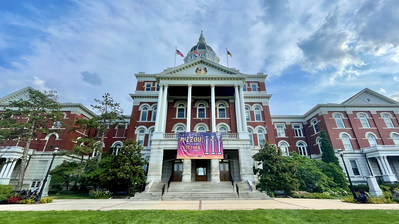 """jesse hall with """"together for 21 festival"""" banner on it and blue sky above"""