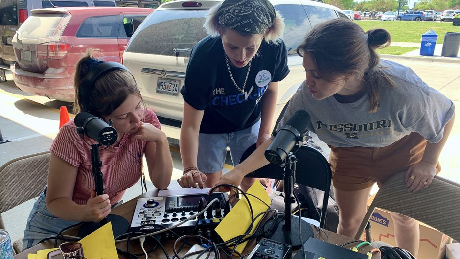 students work outside at an audio booth