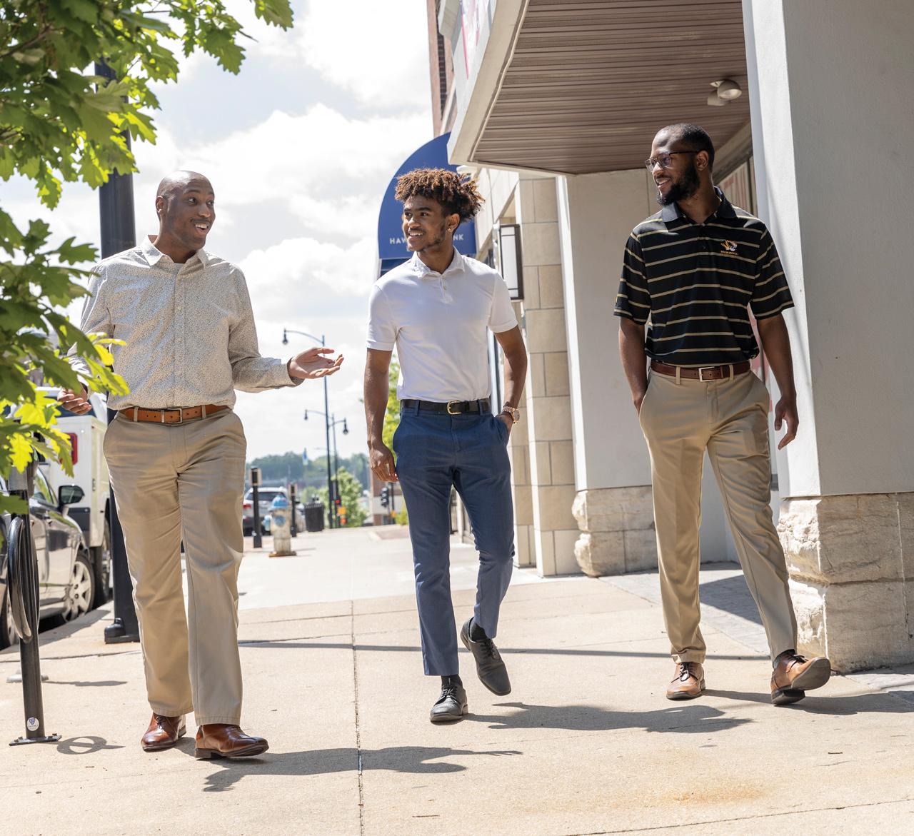 three young men walking on sidewalk downtown Columbia