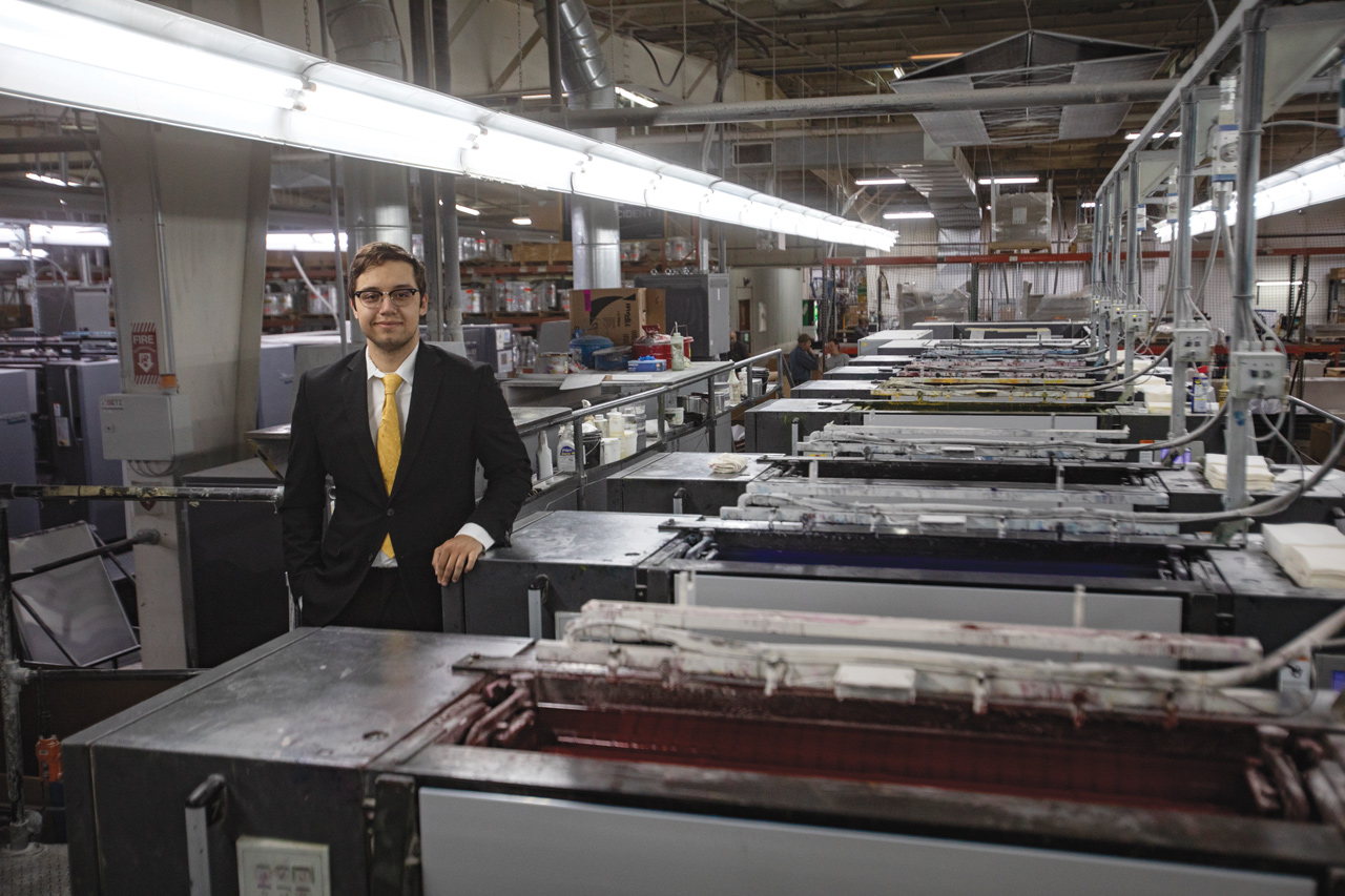 young man inside printing plant