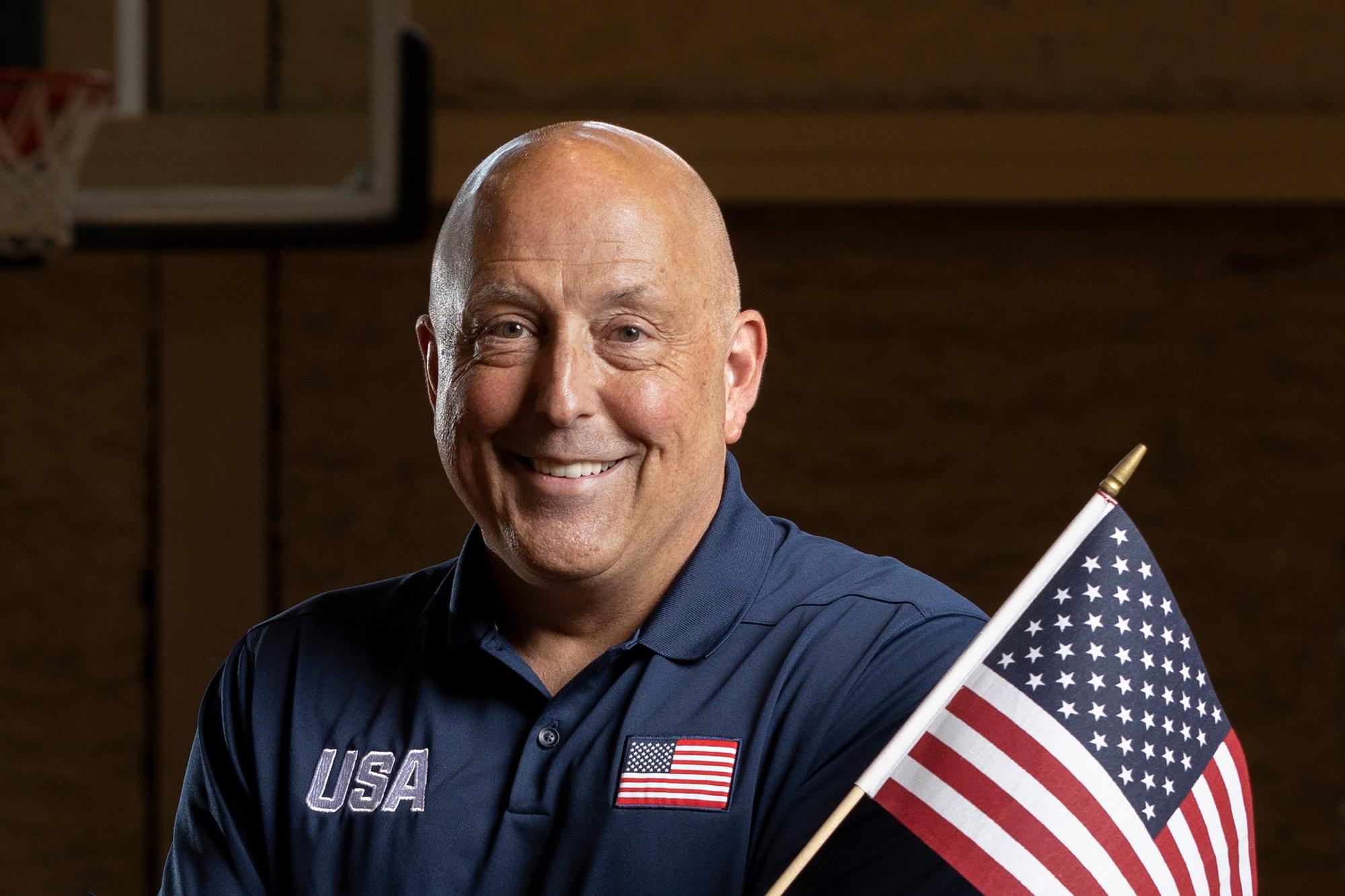 coach ron lykins in a team USA shirt with an american flag