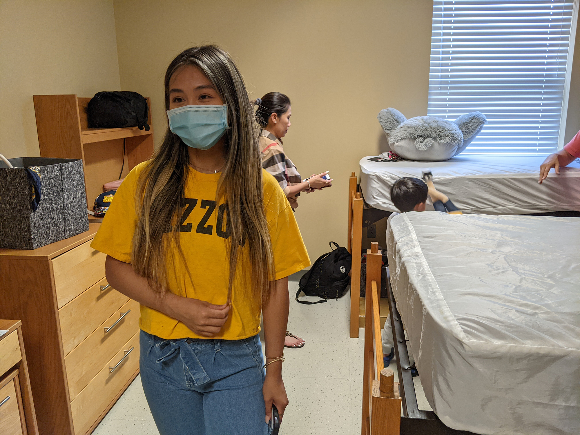 a girl smiling with a face mask in a dorm room