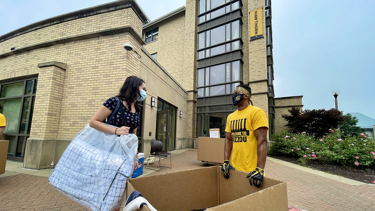 a woman and a man stand outside hawthorn dorm, moving in